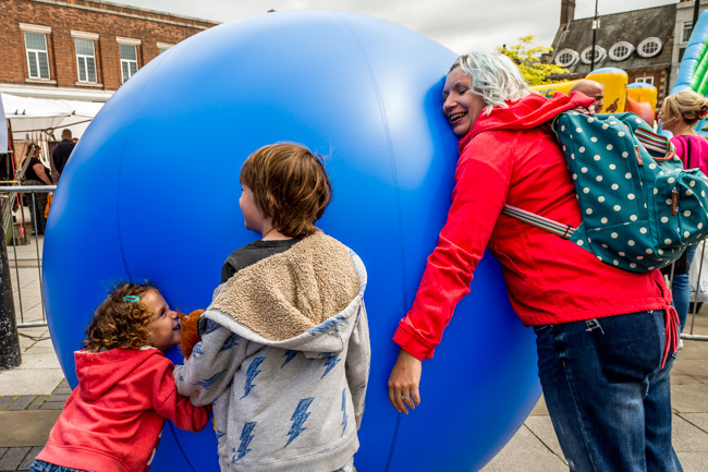 Image of Children and adult lean on large inflatable ball - SHIFT