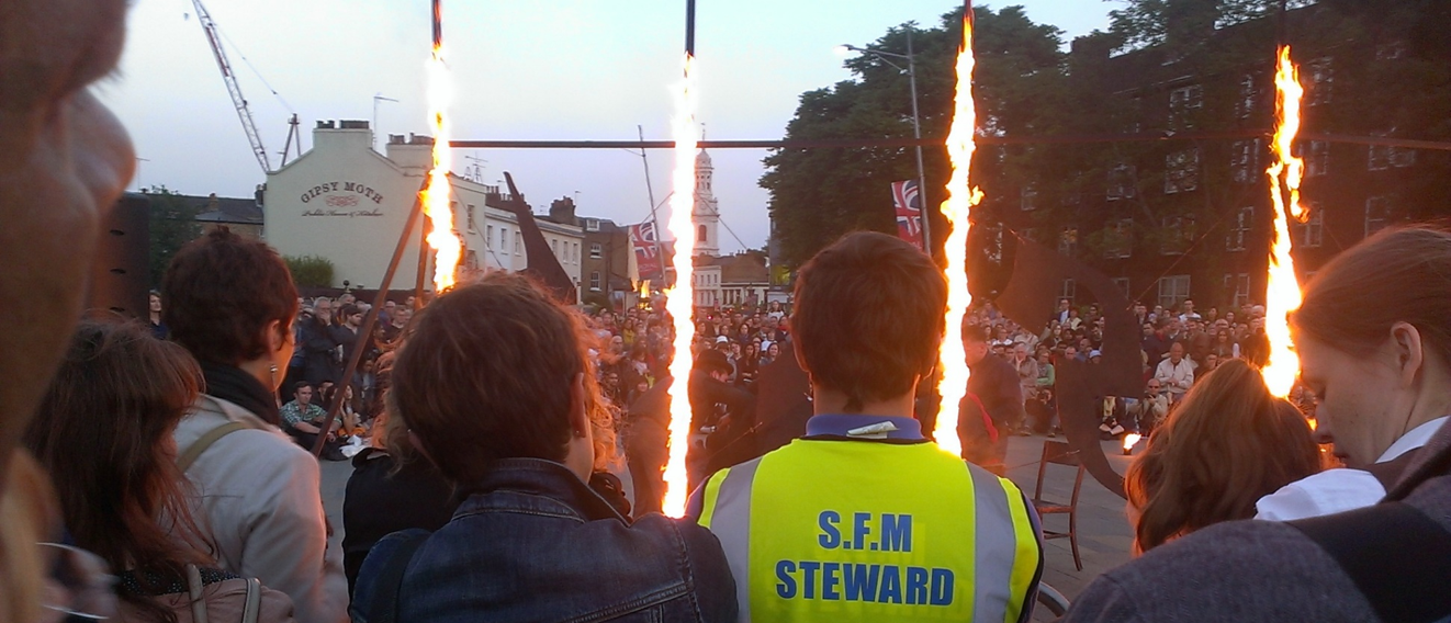 Image of Outdoor arts crowd, fire around performance space