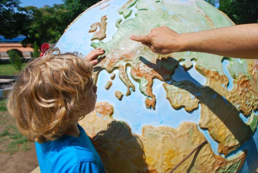 Image of Child with large globe outdoors