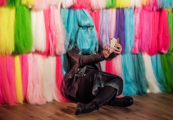 Image of Woman taking selfie through colourful hair