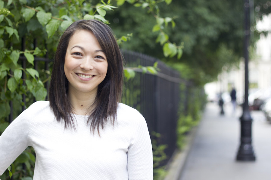 Image of A smiling woman standing on a leafy street
